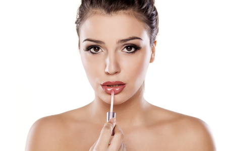 gloss: Woman applying lip gloss