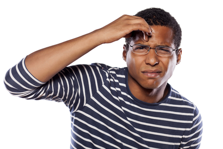business skeptical: unsure dark-skinned young man with glasses trying to focus