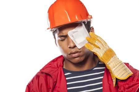 sad donkere werknemer met helm en flaster over zijn gewonde oog Stockfoto