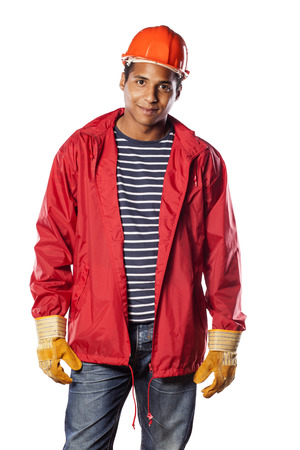 Positive dark-skinned worker with helmet and gloves Stock Photo