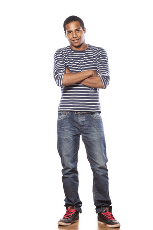 smiling dark-skinned young man in jeans and a blouse