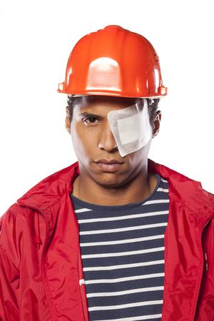 occhi tristi: triste lavoratore dalla pelle scura con il casco e Flaster sopra l'occhio ferito