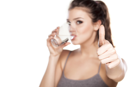 beautiful woman drinking water from a glass and showing thumb up