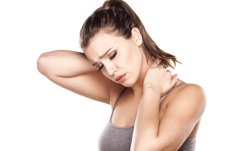 hand on shoulder: beautiful young woman has a pain in the neck Stock Photo