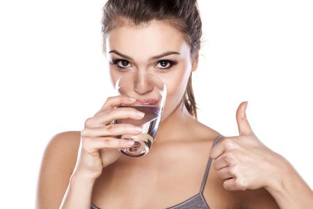 vasos de agua: hermosa mujer de agua potable de un vidrio y mostrando el pulgar Foto de archivo