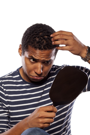 concerned dark-skinned young man settles himself in the mirror Stock Photo