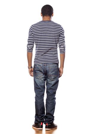 achteraanzicht van donkere jonge man in een spijkerbroek en een blouse Stockfoto