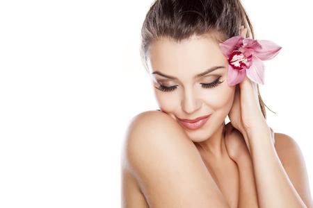 modelo: joven y bella mujer posando con la orquídea en el fondo blanco