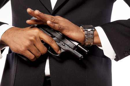 Dark-skinned businessman recharging his gun