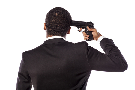 death head holding: African businessman holding a gun on his head Stock Photo
