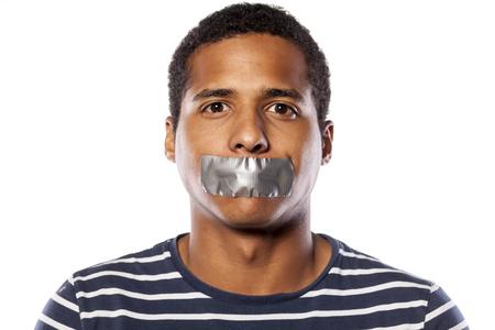 jeune homme à la peau sombre avec du ruban adhésif sur la bouche Banque d'images