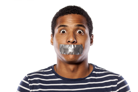 fair skinned: upset dark-skinned young man with adhesive tape over his mouth
