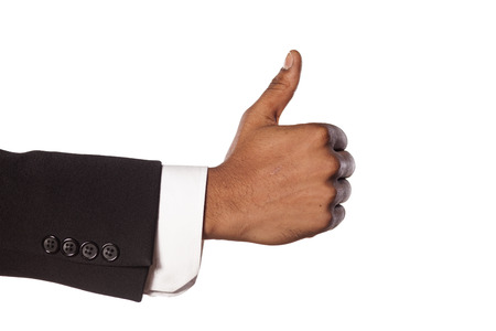 dark skinned: dark skinned hand in a suit showing thumb up Stock Photo