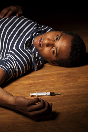 Young dark-skinned man lying on the floor with a syringe next to his hand Stock Photo