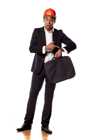 wrist watch: African businessman with a helmet and a briefcase pointing at his wrist watch