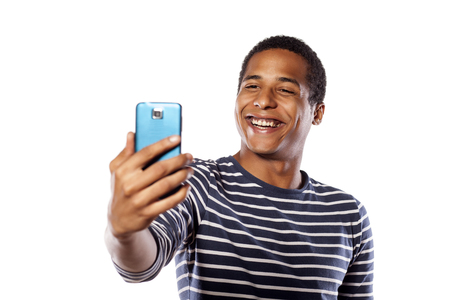 hombres de negro: Sonriente que hace selfie joven de piel oscura sobre un fondo blanco Foto de archivo