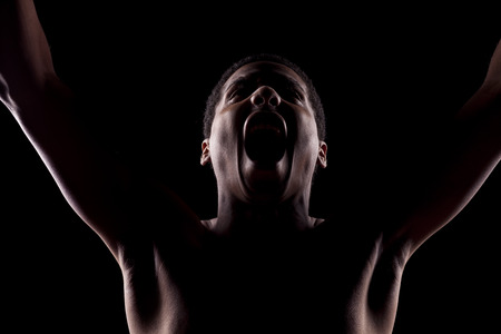 unnamed: screaming unknown man with his face in the shadow and arms up