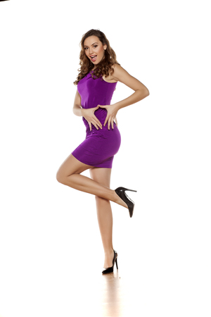 tight: beautiful young woman posing in a violet tight short dress