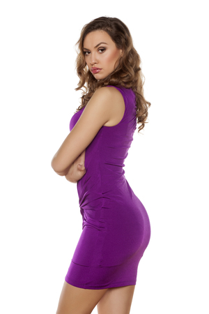 beautiful young woman posing in a violet tight short dress
