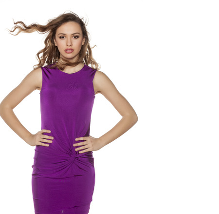 tight: beautiful young woman with wavy hair posing in a violet tight short dress Stock Photo