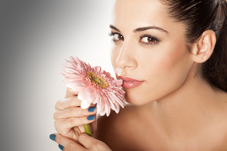 scent: young beautiful woman enjoying the scent of the flower gerbera Stock Photo