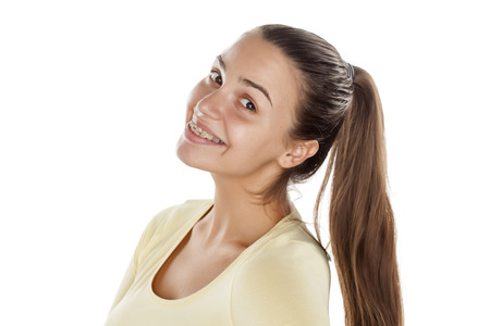 young smiling woman with a ponytail posing on a white background
