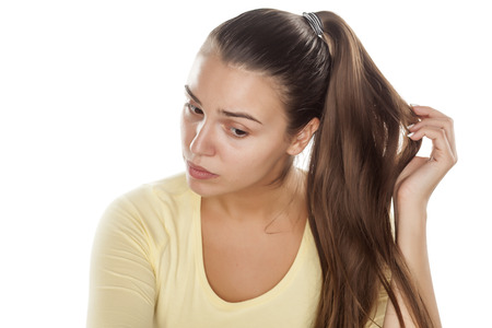 ponytail: young woman without makeup touching her ponytail Stock Photo