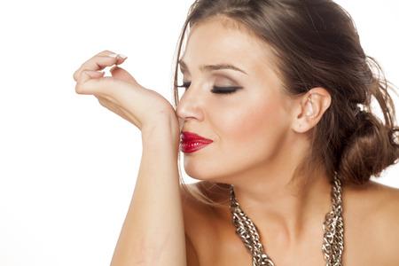 Schöne junge Frau, die den Geruch des Parfüms auf ihrem Handgelenk genießen Standard-Bild - 57194192
