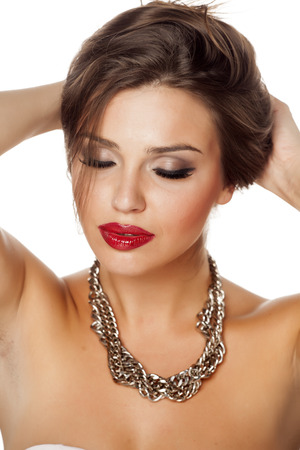 fake eyelashes: a young beautiful woman with closed eyes posing with a big necklace Stock Photo