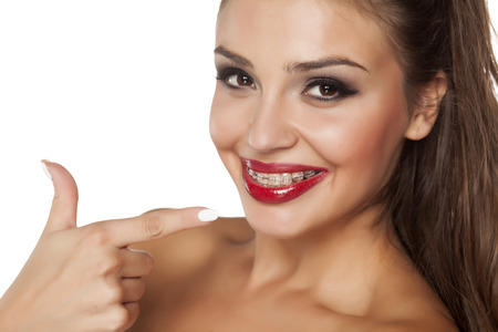 pretty young woman pointing a finger at her braces