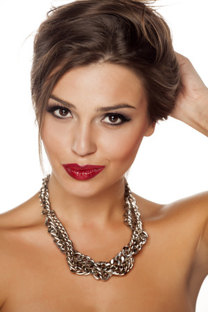fake smile: young beautiful woman posing with a big necklace