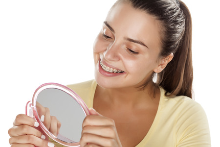 no teeth smile: young woman looking at her braces in the mirror