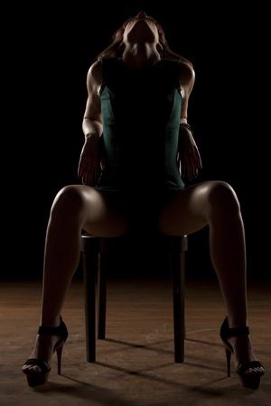 Frau auf einem Stuhl in der Dunkelheit mit gespreizten Beinen sitzt