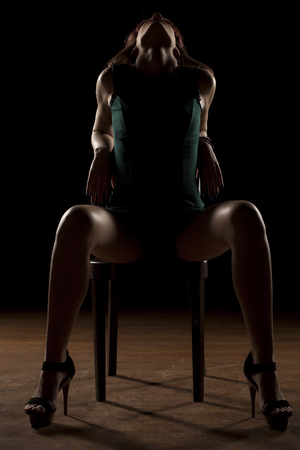 legs wide open: woman sitting on a chair in the dark with spread legs Stock Photo