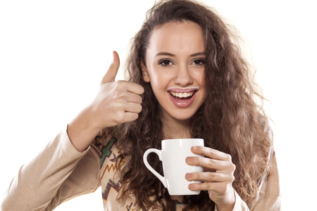 milk mustache: young girl holding a cup of milk and showing thumb up