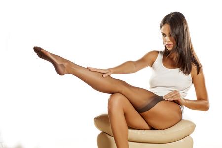 pantimedias: hermosa mujer joven y atractiva que pone en sus medias de nylon