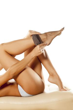 woman putting on her nylon stockings Stock Photo