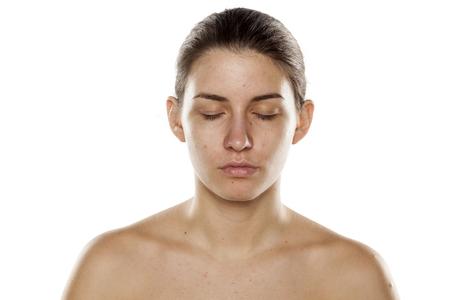 cabeza femenina: serio de la mujer joven y bella sin maquillaje y con los ojos cerrados sobre un fondo blanco