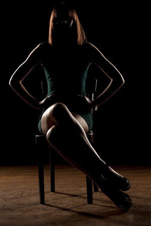 unrecognizable woman sitting in the dark on a chair with her legs crossed