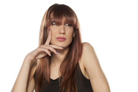 young woman with bangs posing on a white background
