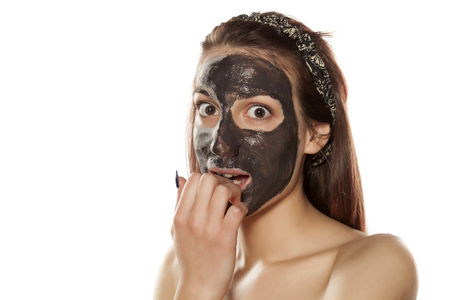mud woman: surprised young woman with mud mask on her face