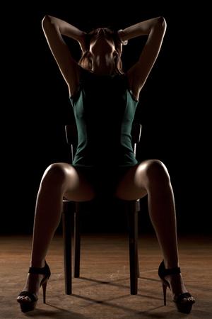 beine spreizen: Frau auf einem Stuhl in der Dunkelheit mit gespreizten Beinen sitzt