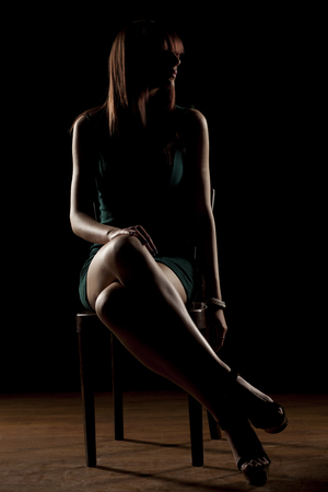 lady silhouette: unrecognizable woman sitting in the dark on a chair with her legs crossed