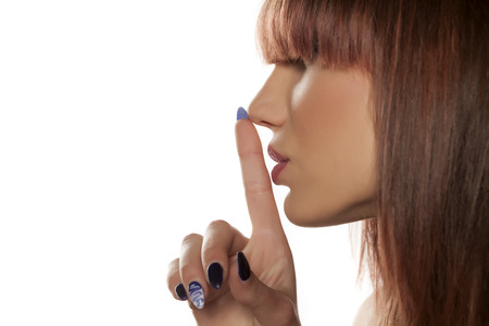 profile of a young woman with bangs, and with finger on her lips. silence gesture
