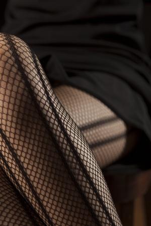 model fish: feminine crossed legs in fishnet stockings