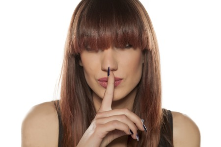 shush: young woman with bangs and with finger on her lips. silence gesture