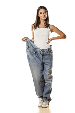 happy pretty attractive girl posing in big size pants on a white background Standard-Bild