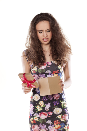 unhappy girl opening a gift that is not satisfied Stock Photo