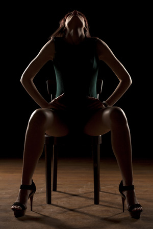 lady silhouette: woman sitting on a chair in the dark with spread legs Stock Photo