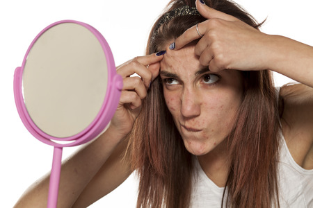 young woman squeezing her acne in front of a mirror